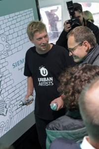 Berlins Bürgermeister Müller besucht die Digitale Graffiti Wand.